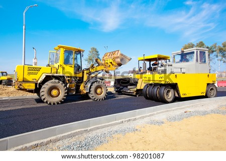 road under construction - wheel loader machine, pneumatic tyred roller and tracked paver at asphalt pavement works - stock photo