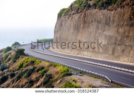 Road under the rock near the sea. - stock photo