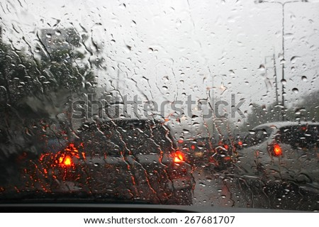 Road view through car window with rain drops, Driving in rain. - stock photo