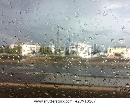 Road view through car window with rain drops, Driving in rain. - stock photo