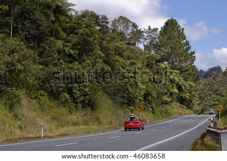 Road with a red car near Whangarei - stock photo