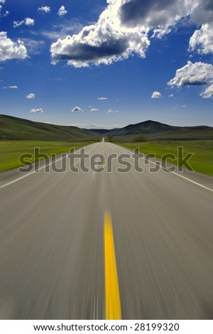 Road with blue sky and clouds blurry motion to indicate speed - stock photo