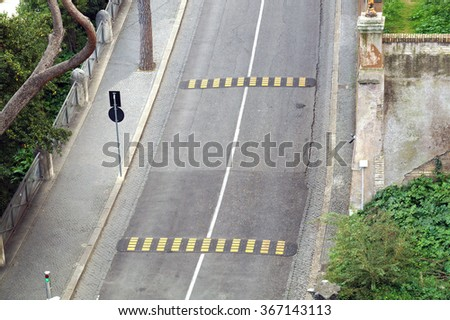 road with bumps to reduce speed - stock photo