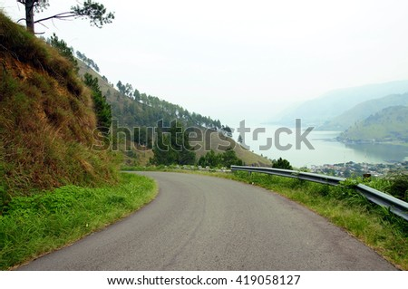 road with hill and lake - stock photo