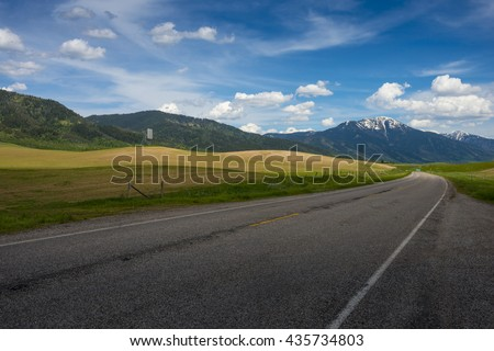 Road with one point perspective driving car to rugged rocky Teton snow capped mountain range blue sky majestic landscape scene with dramatic clouds - stock photo