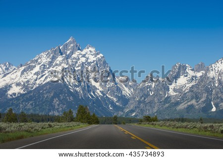 Road with one point perspective driving car to rugged rocky Teton snow capped mountain range blue sky majestic landscape scene  - stock photo