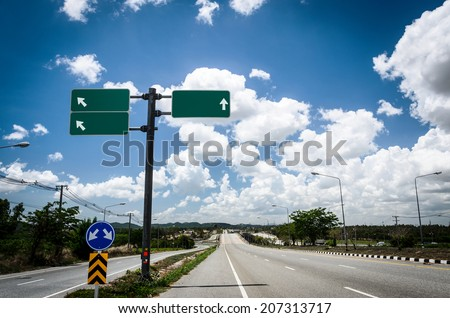 road with sign pole and blue sky with clouds - stock photo
