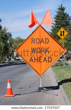 Road Work Ahead sign and orange cone standing in the street. - stock photo