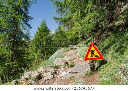 Road work sign on a path ascending into a forest. - stock photo