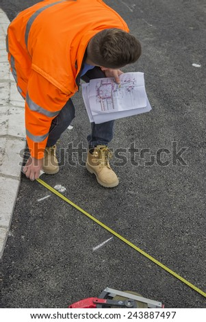 Road worker marking asphalt for painting pedestrian crosswalk - stock photo