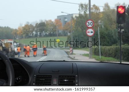 Road workers at the asphalt repairing works  - stock photo