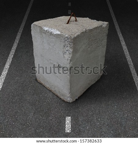 Roadblock obstacle and barrier business concept as a huge cement or concrete cube barricade blocking a road as a symbol of restricted opportunity or political gridlock or financial system shutdown. - stock photo