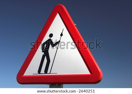 roadside warning sign with an image of a walking man - stock photo