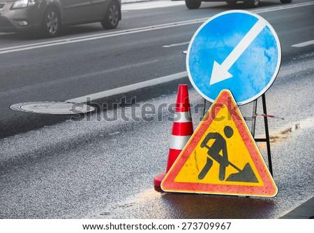Roadsigns on the urban asphalt road. Men at work - stock photo