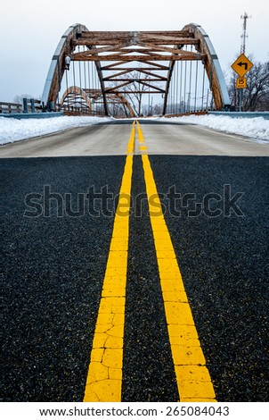 Roadway yellow lane leading to complex modern geometrical bridge. Concrete cement road blacktop with yellow line.  - stock photo