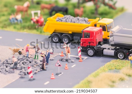 Roadworks with miniature figurines in a country setting close up - stock photo