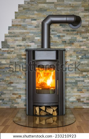 Roaring fire inside wood burning stove in living room - stock photo
