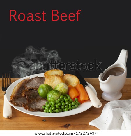 Roast Beef Concept - steaming hot roast beef with roast potatoes, brussels sprouts, carrots, peas and a jug of gravy, on a dark background with the words Roast Beef.  - stock photo