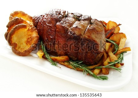 roast beef joint with roast vegetables - stock photo