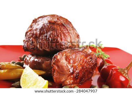 roast beef meat fillet medallion with cherry tomatoes and hot peppers on red plate isolated on white background - stock photo