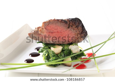 Roast beef on a nest of spinach leaves and garlic - stock photo