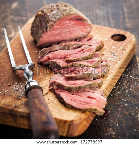 Roast beef on cutting board and meat fork - stock photo