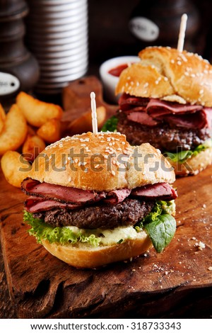 Roast beef or pastrami burger on a sesame bun with salad trimmings on a wooden counter in a fast food restaurant for a delicious snack or pub lunch - stock photo