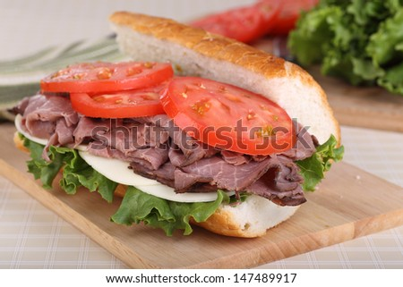 Roast beef sandwich with lettuce, cheese and tomato on french bread - stock photo