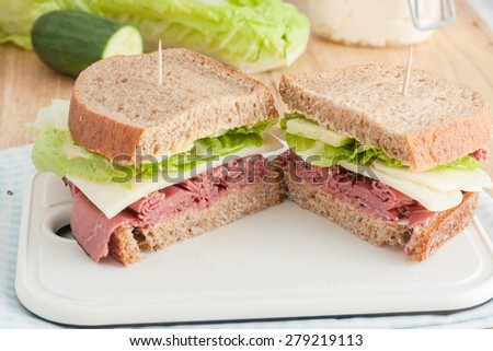 roast beef sandwich with lettuce made with whole wheat bread on white cutting board - stock photo