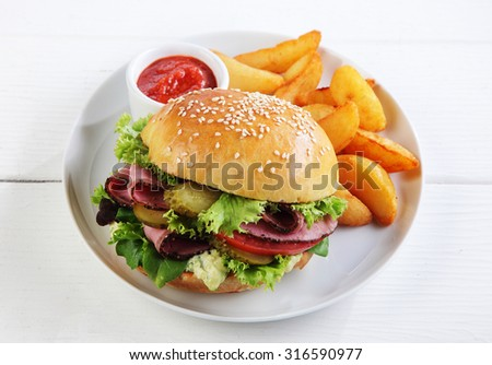 Roast beef sesame roll with salad trimmings served with French fries or potato wedges and tomato ketchup on a plate, high angle view on a white wooden table - stock photo