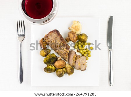 Roast beef with grilled vegetables with glass of red wine on served table. Top view image. Meat with roast mushrooms, broccoli and brussels sprouts on white dish - stock photo