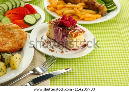 Roast chicken cutlet with boiled potatoes and  vegetables, cup of tea and dessert, on green table cloth - stock photo