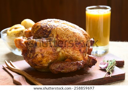 Roast chicken on wooden board with potatoes and juice in back, photographed with natural light (Selective Focus, Focus on the front of the chicken)   - stock photo