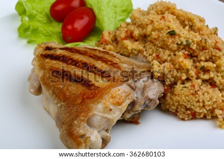 Roast chicken with couscous, salad leaves and tomato - stock photo