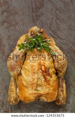 Roast chicken with fresh herbs.  Overhead view, on rustic stone background. - stock photo