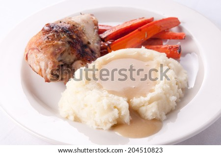 roast chicken with mashed potatoes, vegetables and smothered with creamy, rich gravy - stock photo