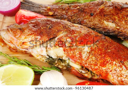 roast golden fish on wooden plate served with lemon and salad - stock photo