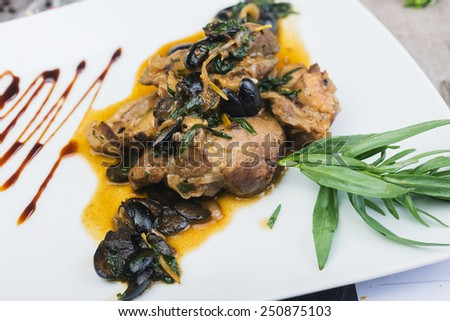 Roast lamb chops with black olives  on a plate on a wooden table in a restaurant - stock photo
