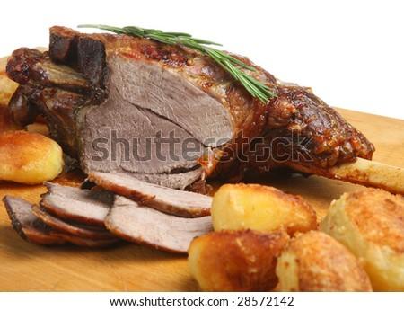 Roast leg of lamb on carving board - stock photo