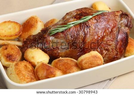 Roast leg of lamb with roast potatoes - stock photo