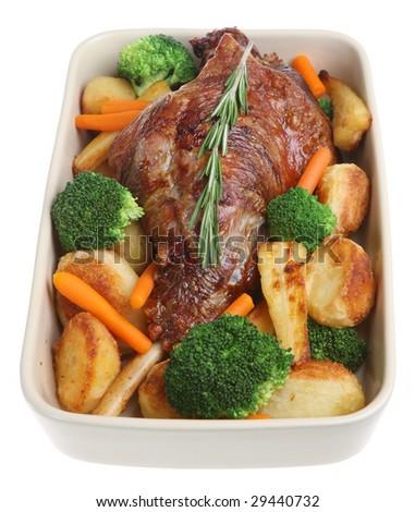 Roast leg of lamb with roast potatoes and vegetables - stock photo