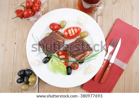 roast meat : beef (pork) steak garnished with baked apples , juice, green and black olives , tomatoes , on wooden table - stock photo
