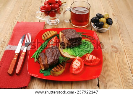 roast meat : beef (pork) steak garnished with vegetables , juice and olives on red plate over wooden table - stock photo