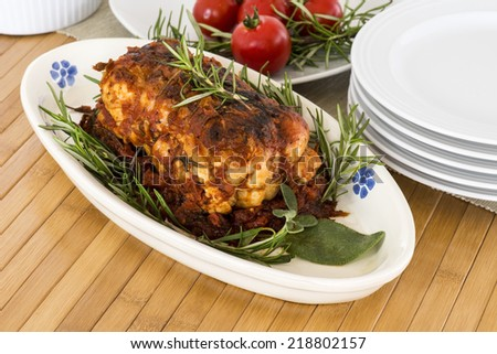 roast of veal  with rosemary and tomatoes on wooden table - stock photo