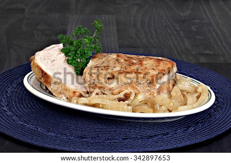 Roast pork loin with onions.  Close up with copy space. - stock photo