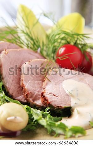 Roast pork tenderloin with vegetables - stock photo