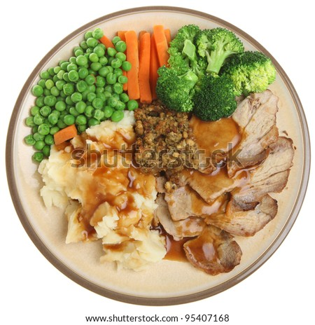Roast pork with mashed potato, vegetables, stuffing and gravy. - stock photo