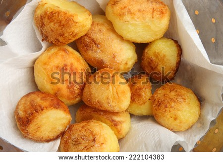 Roast potatoes draining on kitchen paper - stock photo