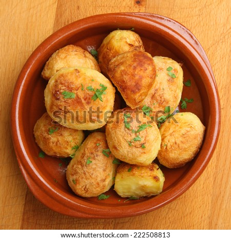 Roast potatoes in terracotta serving dish. - stock photo