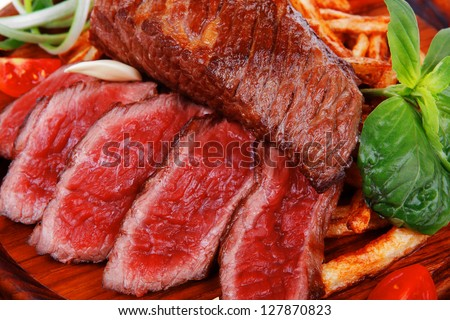 roast steak on potato : fresh grilled beef meat on wood plate with pepper and tomato isolated on white background - stock photo